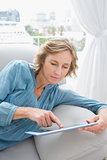 Content blonde woman relaxing on her couch using her tablet