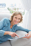 Happy blonde woman relaxing on her couch using her tablet