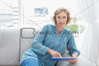 Blonde woman relaxing on her couch using her tablet