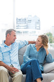 Cheerful couple relaxing on their couch having a chat