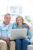 Smiling couple relaxing on their couch using the laptop