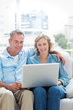 Smiling couple sitting on their couch using the laptop
