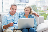 Smiling couple sitting on their couch using the laptop to buy online