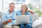 Happy couple sitting on their couch using the laptop to buy online