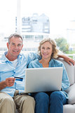 Cheerful couple sitting on their couch using the laptop to buy online