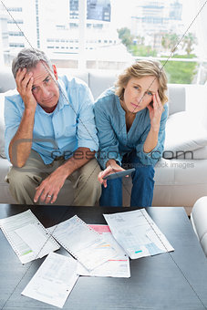 Anxious couple sitting on their couch paying their bills