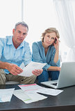 Anxious couple paying their bills online with laptop looking at camera
