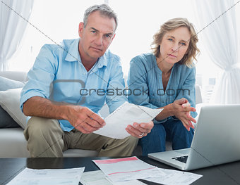 Worried couple paying their bills online with laptop looking at camera