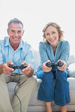 Smiling couple playing video games together on the couch