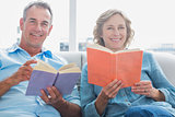 Relaxed couple reading books on the couch smiling at camera