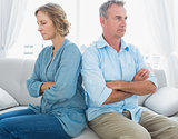 Middle aged couple sitting on the couch not speaking after a fight