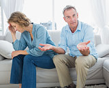 Arguing middle aged couple sitting on the couch with man gesturing at camera