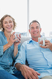 Happy middle aged couple sitting on the couch having coffee