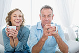 Content middle aged couple sitting on the couch having coffee