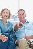 Cheerful middle aged couple sitting on the couch watching tv