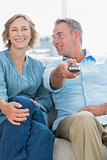 Cheerful couple sitting on the couch watching tv