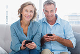 Happy couple using their smartphones