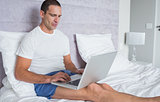 Concentrating man using laptop on bed