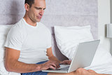 Serious man using laptop on bed