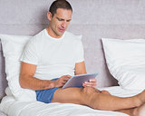 Cheerful man using tablet pc on bed