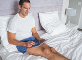 Smiling man using his tablet pc on bed
