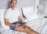 Smiling man using his tablet pc sitting on bed