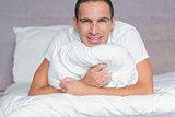 Happy man hugging his pillow