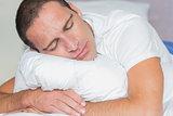 Sleeping man hugging his pillow