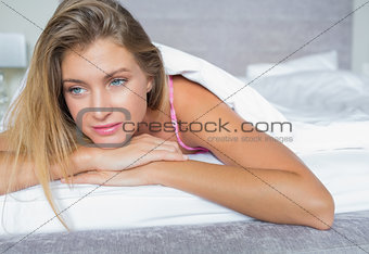 Beautiful blonde lying in her bed thinking