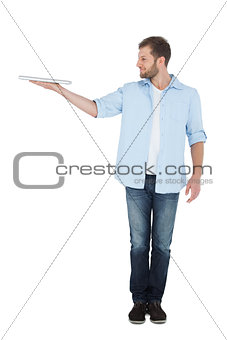 Cheerful model holding laptop on right hand