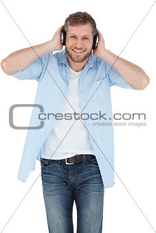 Trendy model listening to music and looking at camera