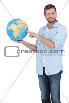 Casual man holding a globe