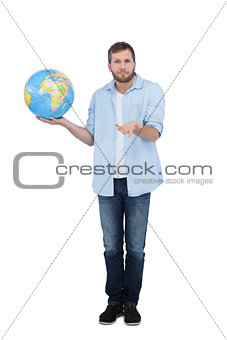 Charming model holding a globe and shrugging shoulders