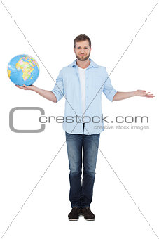 Charming young model holding a globe and looking at camera