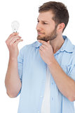 Sceptical model holding a bulb and touching his chin