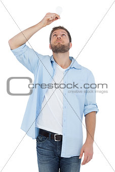 Sceptical model holding a bulb above his head