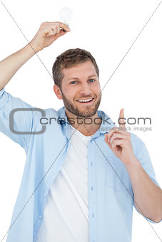 Smiling model holding a bulb above his head