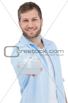 Portrait of smiling young model offering gift