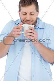 Casual model having coffee and smelling it