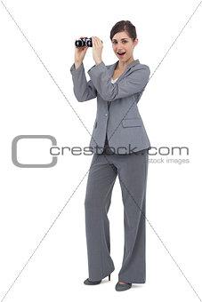 Astonished businesswoman posing with binoculars
