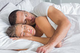 Cute couple sleeping and cuddling in bed