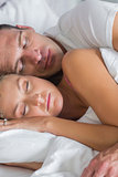Attractive couple sleeping and spooning in bed