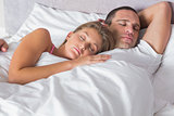 Attractive couple sleeping and cuddling in bed