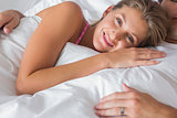 Smiling woman lying on husbands chest in bed