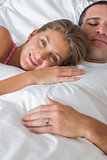 Happy woman lying on husbands chest in bed