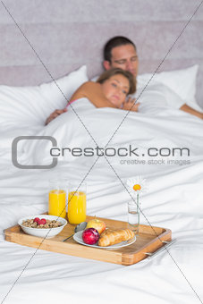 Attractive couple asleep with breakfast tray on bed