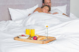Cuddling couple asleep with breakfast tray on bed