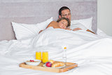 Attractive couple sleeping with breakfast tray on bed