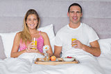 Happy young couple having breakfast in bed