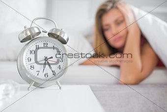 Tired blonde staring at her alarm clock